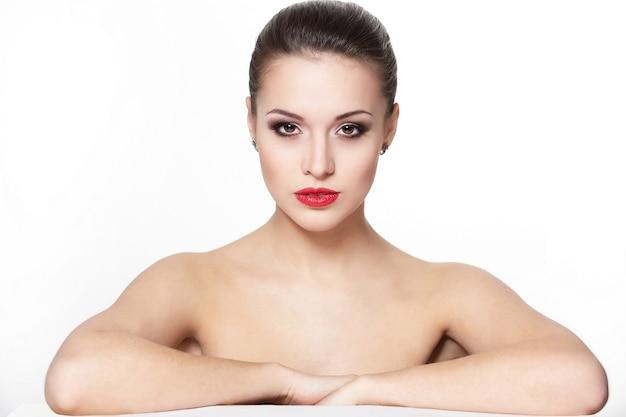 Portret seksowny poważnie siedzący kaukaski młoda kobieta model z czerwonymi ustami glamour, jasny makijaż, makijaż strzałka w oko, cera czystości. idealnie czysta skóra