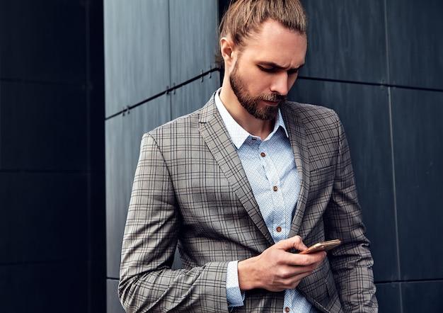Portret seksowny przystojny mężczyzna ubrany w elegancki beżowy garnitur w kratkę