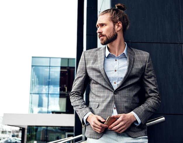 Portret seksowny przystojny mężczyzna ubrany w elegancki szary garnitur w kratkę