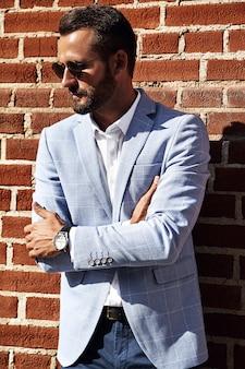 Portret seksowny przystojny moda biznesmena model ubierał w eleganckim błękitnym kostiumu pozuje blisko ściana z cegieł na ulicznym tle. metroseksualny