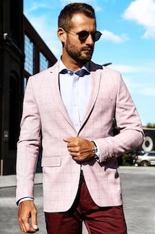 Portret seksowny przystojny moda biznesmena model ubierał w eleganckim kostiumu pozuje na ulicznym tle. metroseksualny