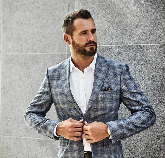 Portret seksowny przystojny moda biznesmena model ubierał w eleganckim w kratkę kostiumu pozuje blisko szarości ściany na ulicznym tle. metroseksualny