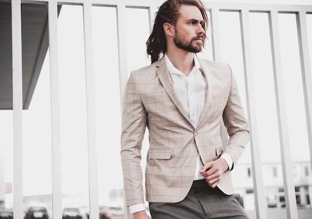 Portret seksowny przystojny moda mężczyzna model mężczyzna ubrany w elegancki beżowy garnitur w kratkę