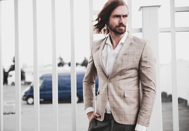 Portret seksowny przystojny moda mężczyzna model mężczyzna ubrany w elegancki beżowy kratkę garnitur pozowanie na tle ulicy