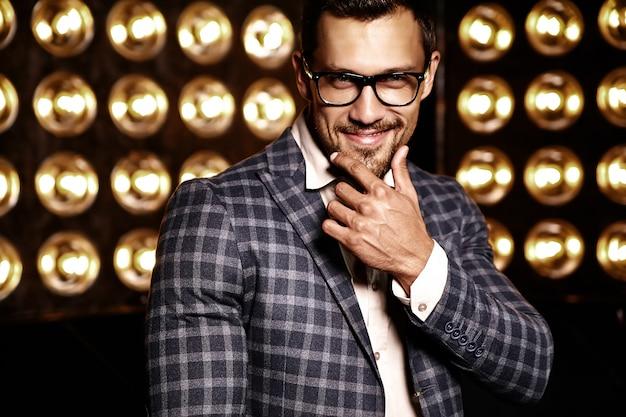 Portret seksowny przystojny moda mężczyzna model mężczyzna ubrany w elegancki garnitur na czarnym tle światła studio w okularach