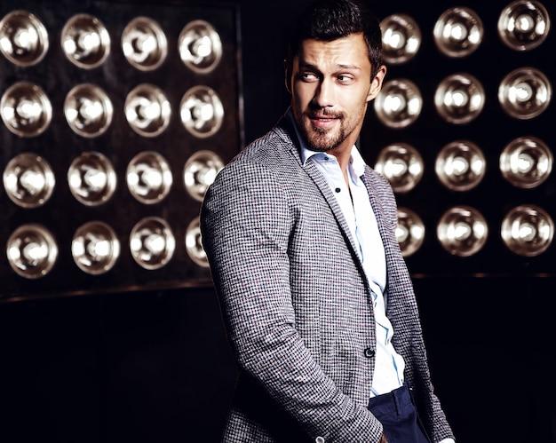 Portret seksowny przystojny moda mężczyzna model mężczyzna ubrany w elegancki garnitur na czarnym tle światła studio