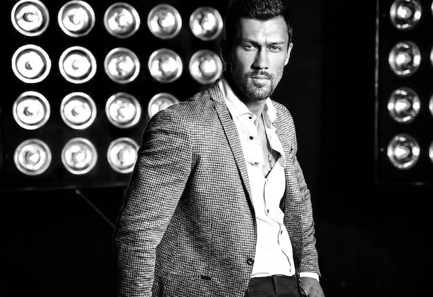 Portret seksowny przystojny moda mężczyzna model mężczyzna ubrany w elegancki garnitur na tle światła studio