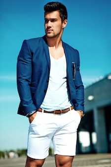 Portret seksowny przystojny moda mężczyzna model mężczyzna ubrany w elegancki garnitur pozowanie na tle ulicy. niebieskie niebo