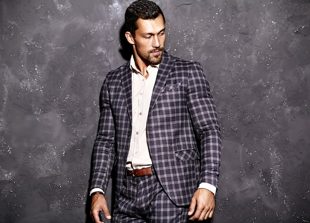 Portret seksowny przystojny moda mężczyzna model mężczyzna ubrany w elegancki garnitur pozowanie w pobliżu szarej ścianie
