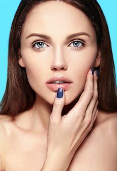 Portret seksowny uroda zbliżenie model piękny zmysłowy kaukaski młoda kobieta z nagim makijażu dotykając jej idealnie czystą skórę na białym tle na niebieskim tle