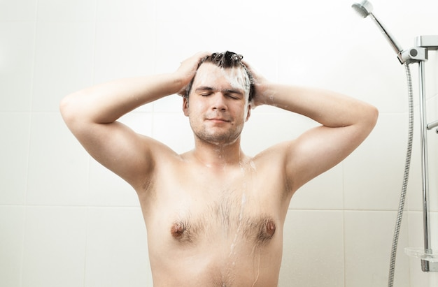 Portret seksowny uśmiechnięty mężczyzna myjący włosy pod prysznicem
