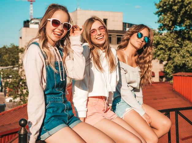 Portret seksownych beztroskich kobiet siedzi na poręczy ulicy. pozytywne modele zabawy w okularach przeciwsłonecznych