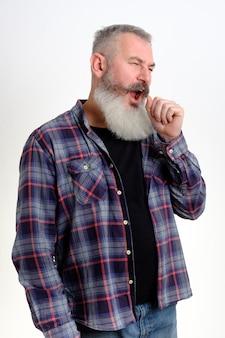 Portret senny dojrzały brodaty mężczyzna w ubranie, ziewanie i zakrywanie ust ręką