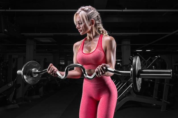 Portret sexy sportsmenka ze sztangą na siłowni. koncepcja fitness.