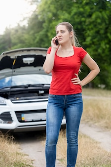 Portret sfrustrowanej kobiety wzywającej pomocy ze swoim zepsutym samochodem na wiejskiej drodze