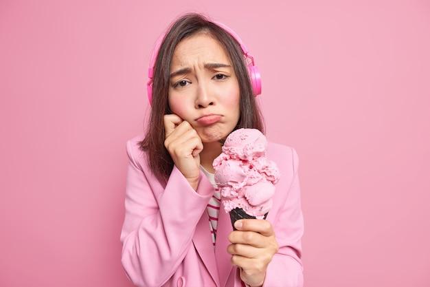 Portret sfrustrowanej młodej azjatyckiej kobiety o ciemnych włosach wygląda nieszczęśliwie torebki usta chce płakać trzyma pyszne lody czuje się samotny nosi bezprzewodowe słuchawki izolowane nad różową ścianą
