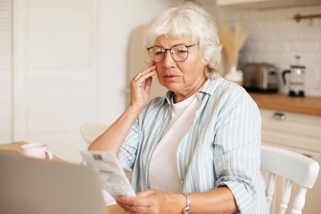 Portret sfrustrowanej siwowłosej emerytki w okularach siedzącej przy kuchennym stole z laptopem, trzymającej rachunek i dotykającej twarzy, zszokowana kwotą całkowitej kwoty za prąd