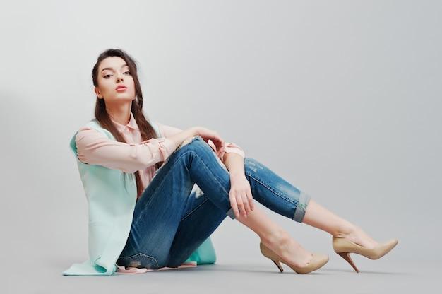 Portret siedzący młoda brunetka dziewczyna ubrana w różową bluzkę, turkusową kurtkę, zgrywanie dżinsy i kremowe buty na szarym tle