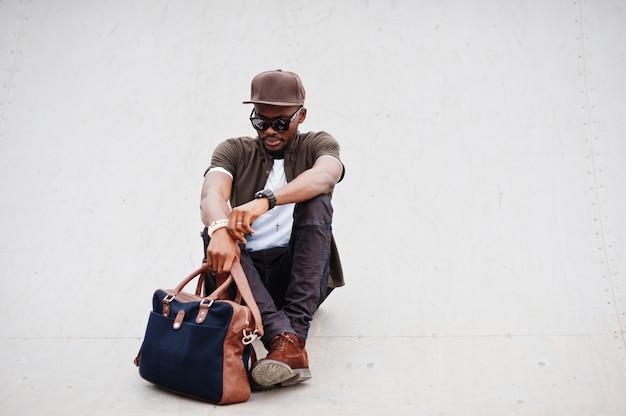 Portret siedzieć elegancką amerykanina afrykańskiego pochodzenia mężczyzna odzież na okularach przeciwsłonecznych i nakrętce z torebką plenerową. murzyn mody ulicznej.
