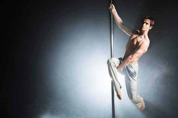 Portret silnego modelu mężczyzna wykonujący taniec na rurze