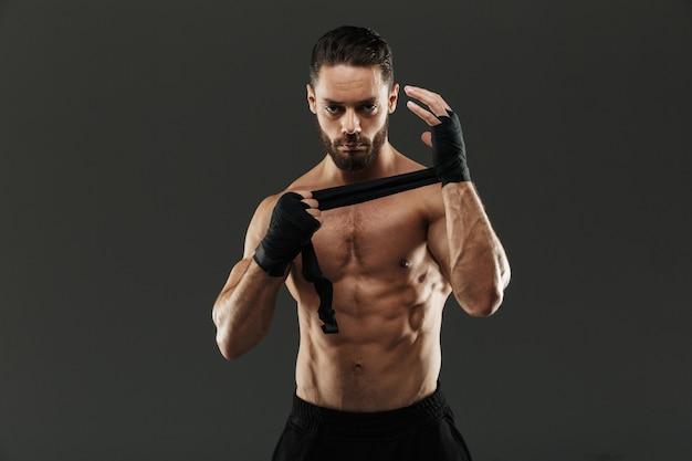 Portret silnego, muskularnego mężczyzny wiążącego bandaże bokserskie