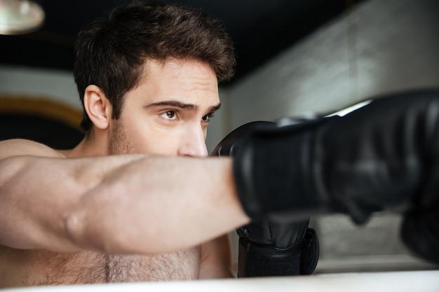 Portret silnego uważnego boksera wykonującego kopnięcie