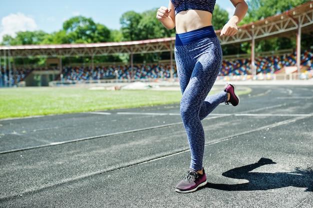 Portret silnej, dopasowanej dziewczyny w odzieży sportowej na stadionie.