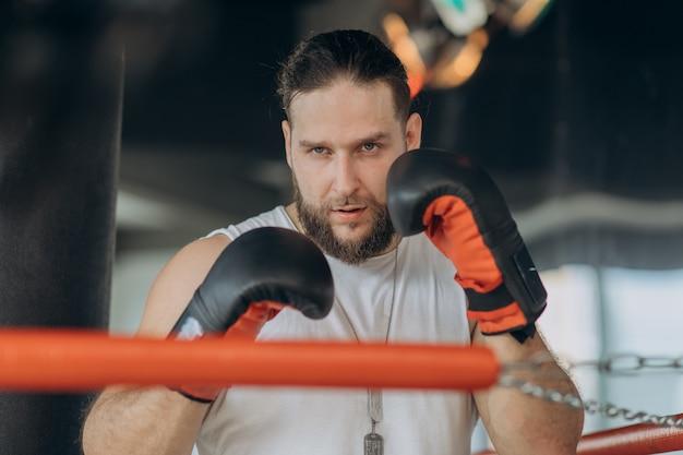 Portret silny mężczyzna patrzeje kamerę na bokserskim pierścionku