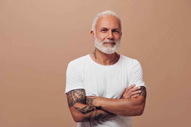 Portret siwego mężczyzny w białej koszuli na izolowanej ścianie