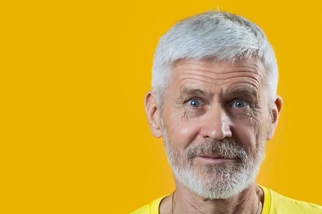 Portret siwego mężczyzny z brodą pokazuje dobry gest na niebiesko