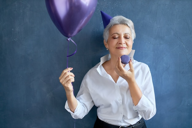 Portret siwowłosej babci w stylowej białej koszuli świętującej urodziny, zamykającej z przyjemnością oczy