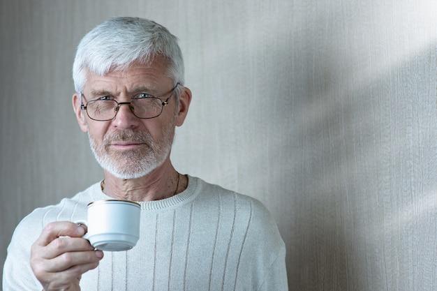 Portret siwy mężczyzna trzyma filiżankę kawy