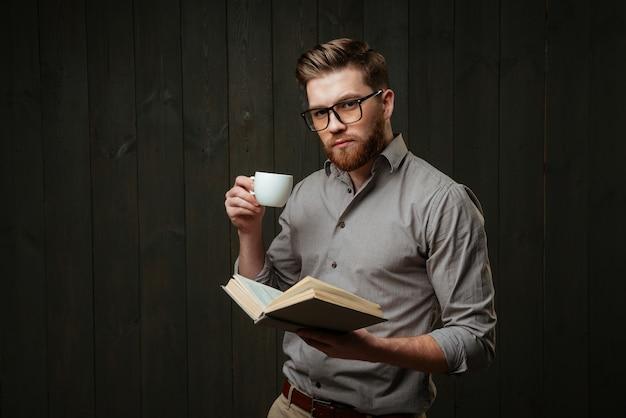 Portret skoncentrowanego brodatego mężczyzny trzymającego otwartą książkę i pijącego kawę na białym tle na czarnej drewnianej powierzchni