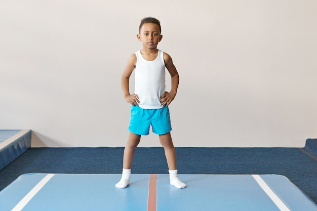 Portret skoncentrowanego ciemnoskórego chłopca ubranego w białą koszulę