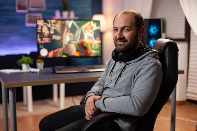 Portret skoncentrowanego gracza w profesjonalnych słuchawkach, grającego w strzelankę online na turniej. cyber działający na potężnym komputerze dzięki strumieniowym grom wideo rgb
