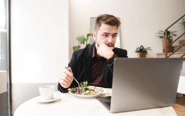 Portret skoncentrowanego mężczyzny siedzącego przy stole w kawiarni z talerzem sałatki i filiżanką kawy i używa laptopa.