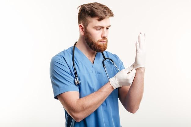 Portret skoncentrowanego młodego lekarza zakładającego sterylne rękawiczki