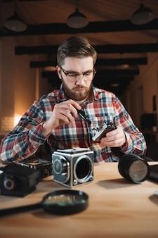 Portret skoncentrowanego młodego mężczyzny naprawiającego retro kamerę w swoim miejscu pracy
