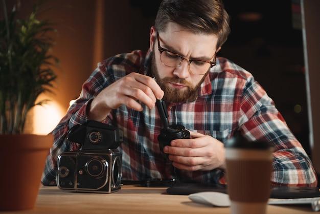 Portret skoncentrowanego młodego mężczyzny naprawiającego stary aparat w swoim miejscu pracy
