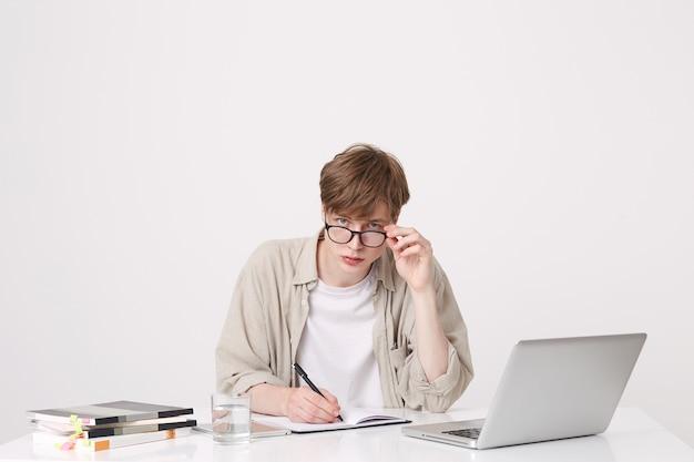 Portret skoncentrowanego młodego ucznia w okularach i beżowej koszuli pisze i uczy się przy stole z laptopem i notebookami odizolowanymi na białej ścianie