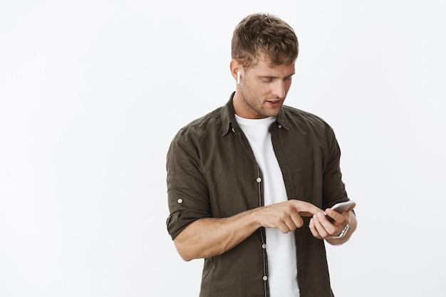 Portret skoncentrowanego, przystojnego faceta w bezprzewodowych białych słuchawkach dousznych, szukającego odpowiedniej muzyki, by załagodzić nastrój, stojącego nad szarą ścianą, dotykającego ekranu i patrzącego na telefon komórkowy, wybierającego piosenkę