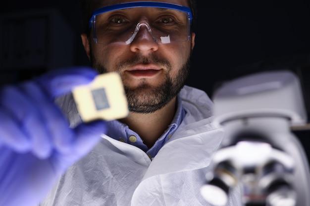Portret skoncentrowanego zawodowego technika w mundurze w pracy. mężczyzna w okularach przyglądający się uważnie mikroukładowi. koncepcja elektroniki i techniki