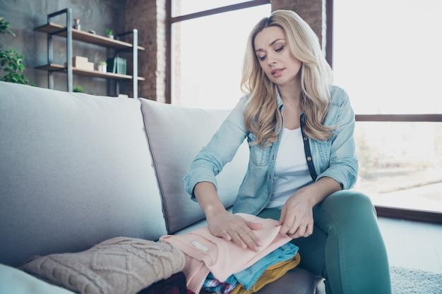 Portret skoncentrowanej gospodyni falistowłosa kobieta siedzi na ubraniach divan pack