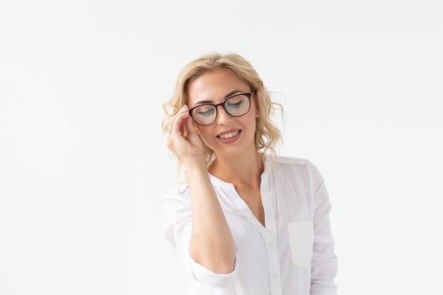 Portret skoncentrowanej pięknej kobiety ze złym wzrokiem dotykając okularów na białym tle