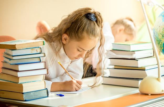 Portret skoncentrowanej uczennicy otoczonej książkami odrabiającymi pracę domową
