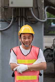 Portret skrzyżowanego ramienia pewnie elektryk lub pracownik konsturacji