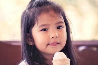 Portret śliczna azjatykcia mała dziewczynka je lody rożek w rocznika koloru brzmieniu