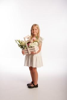 Portret śliczna blondynka w białej sukni z drewnianym koszem kwiatów