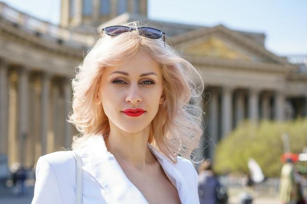 Portret śliczna blondynki kobieta w białej kurtce na ulicie w słonecznym dniu