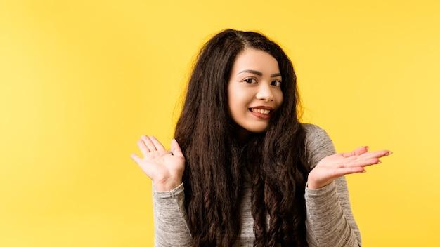 Portret śliczna brunetka dziewczyna. śmieszna emocjonalna dama robiąca niewinny wyraz twarzy, obojętny gest.